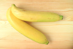 两个充满活力的黄色成熟香蕉顶视图在木表上的 免版税库存图片