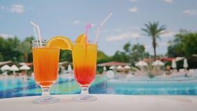 两个凉快的鸡尾酒在水池和棕榈树的背景的桌上站立 天堂和豪华旅游胜地 免版税库存图片