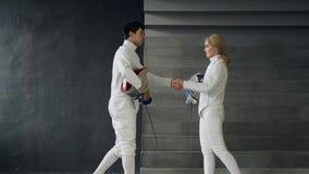 两个击剑者男人和妇女握手在剑术竞争结束时户内 库存图片