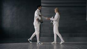 两个击剑者男人和妇女握手在剑术竞争结束时户内 图库摄影