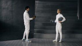 两个击剑者男人和妇女有招呼并且开始操刀比赛户内 库存照片
