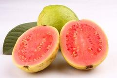 两个切片与叶子的桃红色番石榴果子 库存照片