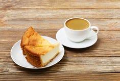 两个切片在一杯白色茶碟和咖啡的乳酪蛋糕 库存图片