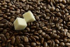 两个切片在咖啡豆背景的糖  免版税库存照片