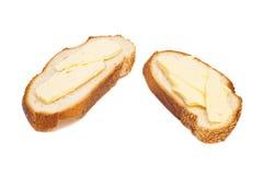 两个切片小麦面包涂用黄油 图库摄影
