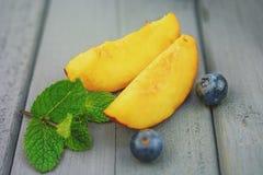 两个切片桃子用在黑暗的背景的蓝莓 免版税库存图片