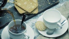 两个切片自创蛋糕和两杯茶在背景中 影视素材
