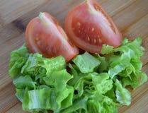 两个切片蕃茄和莴苣在木背景 免版税库存图片