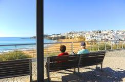 两个前辈坐长凳,阿尔布费拉,海滩阿尔加威,南葡萄牙 库存图片