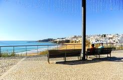 两个前辈坐长凳,阿尔布费拉,海滩阿尔加威,南葡萄牙 库存照片