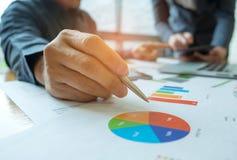 两个办公室工作者分析图表数据,办公室工作者有a 免版税图库摄影