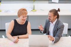 两个办公室工作者在办公室坐 当人告诉某事时,妇女看膝上型计算机 免版税库存照片