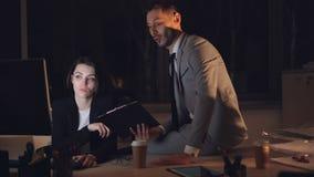 两个办公室工作者男人和妇女一起研究谈话的计算机看屏幕和谈论项目在 股票录像