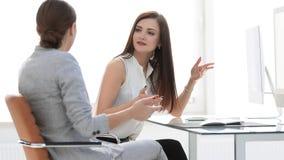 两个办公室工作者谈话在工作场所 免版税库存照片