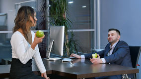 两个办公室工作者食用断裂, aeting的绿色苹果和谈话在办公室 库存图片
