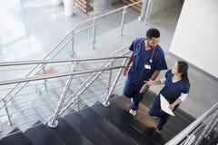 两个医疗保健同事谈话在台阶在医院 免版税库存图片