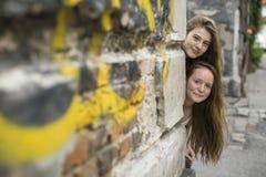 两个十几岁的女孩在房子后的角落看  乐趣 免版税图库摄影