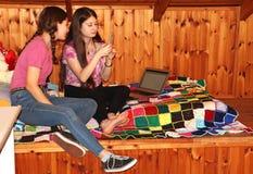 两个十几岁的女孩坐看手机的床 免版税图库摄影
