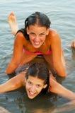 两个十几岁的女孩获得乐趣在河 库存照片