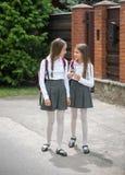 两个十几岁的女孩走在街道上和谈话,当去与学校时 免版税图库摄影
