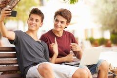 两个十几岁的男孩坐采取Selfie的长凳在公园 免版税图库摄影