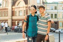 两个十几岁的男孩的友谊和通信是13, 14岁,城市街道背景 免版税库存照片