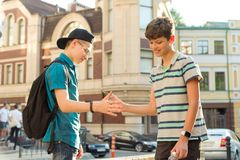 两个十几岁的男孩的友谊和通信是13, 14岁,城市街道背景 免版税图库摄影