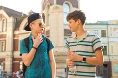 两个十几岁的男孩的友谊和通信是13, 14岁,城市街道背景 库存图片