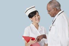 两个卫生业职员有在医疗报告的一次讨论反对浅兰的背景 图库摄影