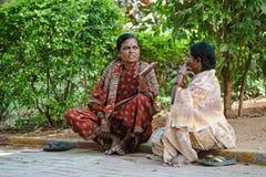 两个印地安人妇女坐地面和讲 Sai 2月8日2018年酵母酒蛋糕聚会所Puttaparthi 免版税库存图片