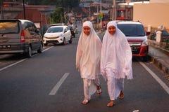 两个印度尼西亚女孩在白色衣裳和hijab的一条城市街道上走 免版税库存图片