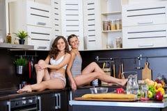 两个双姐妹画象获得乐趣在准备早餐的早晨 免版税库存图片