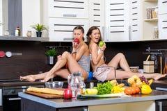 两个双姐妹画象获得乐趣在准备早餐的早晨 图库摄影