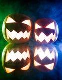 两个发光的南瓜为在蓝色和绿灯的万圣夜 免版税库存照片