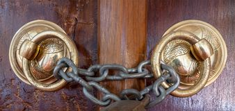 两个古色古香的铜华丽通道门环特写镜头在一个年迈的木华丽门的关闭了与生锈的链子 免版税库存图片
