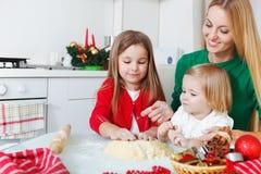 两个可爱的女孩用她的母亲烘烤圣诞节曲奇饼 免版税库存图片
