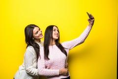 两个可爱的女孩画象在站立和采取在黄色背景的毛线衣穿戴了一selfie 库存图片