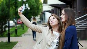 两个可爱的女孩采取在智能手机的照相机的selfie在城市街道上的 股票视频