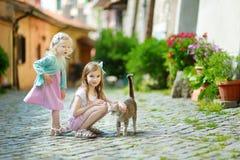 两个可爱的妹和猫 免版税库存照片