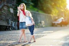 两个可爱的妹获得乐趣一起在温暖和晴朗的夏天晚上在Desenzano del加尔达镇,意大利 免版税图库摄影