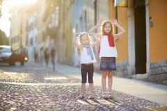 两个可爱的妹获得乐趣一起在温暖和晴朗的夏天晚上在Desenzano del加尔达镇,意大利 免版税库存照片