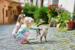 两个可爱的妹遇见了一只猫,当意大利镇时走的狭窄的街道  免版税库存照片