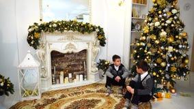 两个可爱的孩子和兄弟在坐在圣诞树下的照相机聊天并且摆在客厅,装饰为 股票视频