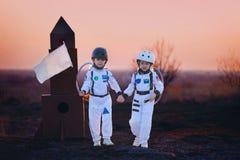 两个可爱的孩子,使用在日落的公园,穿戴了象a 图库摄影