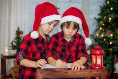 两个可爱的孩子,男孩兄弟,写信给圣诞老人 免版税库存照片