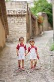两个可爱的孩子,走在街道上,微笑对照相机 免版税图库摄影