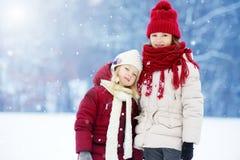 两个可爱的小女孩获得乐趣一起在美丽的冬天公园 使用在雪的美丽的姐妹 免版税图库摄影