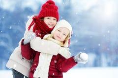 两个可爱的小女孩获得乐趣一起在美丽的冬天公园 使用在雪的美丽的姐妹 图库摄影