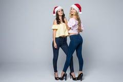 两个可爱的少妇全长画象圣诞节帽子的被隔绝在红色背景 免版税库存图片