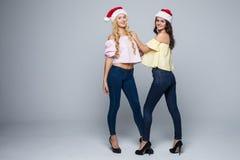 两个可爱的少妇全长画象圣诞节帽子的被隔绝在红色背景 免版税库存照片